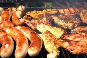 a variety of meats cook on the grill