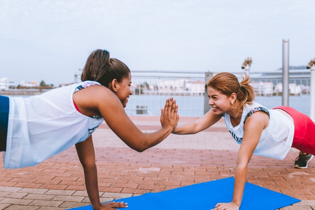 two women high five after reaching your weight loss goals
